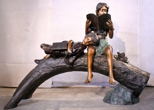 Boy and Girl Reading and Resting on a Log Bronze Sculpture